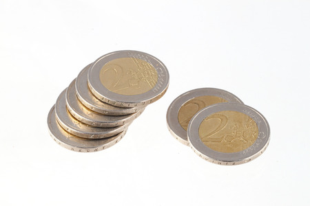 Close up photo of two Euro coins on a plain white background.