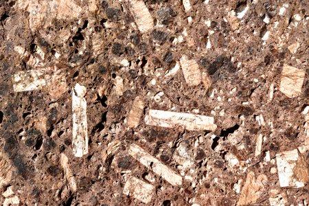A block of weathered red granite, showing large crystals of feldspar, dark hornblende, light quartz, and mica. Stock Photo