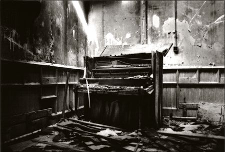 black and white image of a BROKEN PIANO IN A DERELICT BUILDING