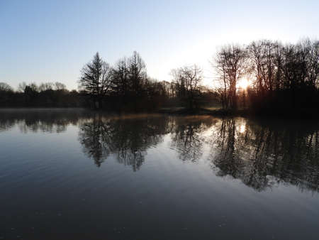 View across Ifield Millpond in Crawley, West Sussex at sunrise on a misty day. Ifield Millpond is a remnant of the 16th century Wealden Iron Industry, where it served as the hammer pond for Ifield