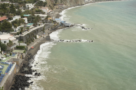 choppy: Ischia Island, the beach of the fumaroles, coastline. Spring day, the sea slightly choppy, cieleo and colors of green, ombrellni, houses and swimming pools.