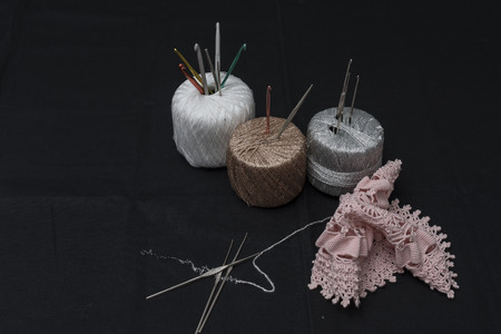 excellent work: Crochet, Italian manufacture. made in Italy. Balls of yarn and crochet for the work of the school of Italian craftsmanship. black background. Examples of complex jobs. Excellent execution. Stock Photo