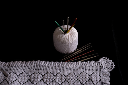 craftsmanship: Crochet, Italian manufacture. made in Italy. Balls of yarn and crochet for the work of the school of Italian craftsmanship. black background. Examples of complex jobs. Excellent execution. Stock Photo