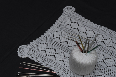 Crochet, Italian manufacture. made in Italy. Balls of yarn and crochet for the work of the school of Italian craftsmanship. black background. Examples of complex jobs. Excellent execution. Stock Photo