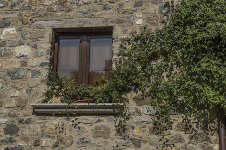 lintels: Old Roscigno, window with ivy and climbing. Wall and sill stone, wood frame, wooden lintel, wooden lintels, rain in brown plate. Stock Photo