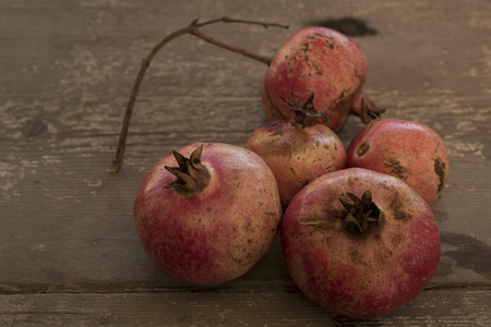 50mm: Five ripe pomegranates, red, on a wooden table. wooden background marroe gray and dark. Fruits on the right side of the shot. Nikon D750, full frame, 50mm Stock Photo