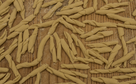 first floor: Fusilli pasta with homemade Italian soft wheat flour type 00, first floor of the dough on the wooden table, stripes and white flour.