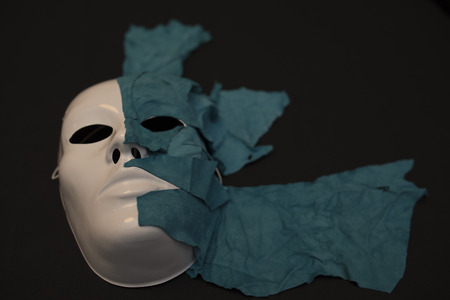 white mask: White Mask on black background covered with skin Stock Photo