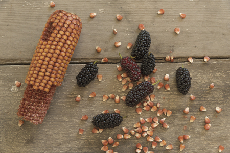 blacks: Bowl of blacks mulberry and corn kernels to pop corn on the rough wooden table.