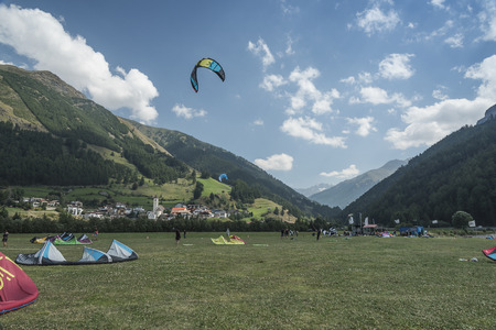 trees services: Reschensee - Italy - Suedtirol - 2015 August 10, Campo kitesurfing school in Curan Venosta. Arrival of groups, arrangement on the lawn to meet and lecture. On the wind-inflated kite background.