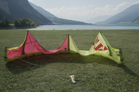 trees services: Lake Resia, Italy, South Tyrol, August, school, kitesurfing, Curon Venosta, kite inflated by the wind, ready for takeoff. yellow and red, in the background the green water of the lake