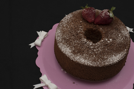 donut strawberry with icing sugar and strawberry on pink and white tablecloth  tray.