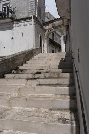 ali angelo: scale bianche e ripide contro la città vecchia. bianco arco in pietra beteween due edifici.