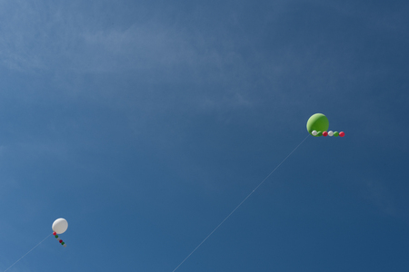 attached: White heelium ballons, red and green, attached to wire in a blue sky