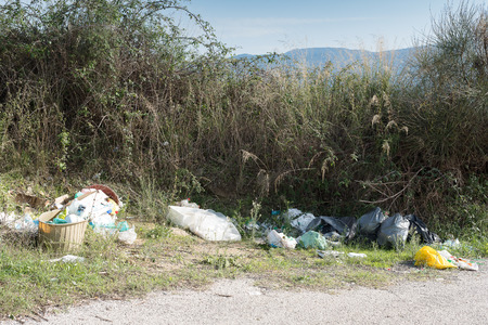 envelops: Envelopes, tires, plastic bottles, and other waste left on the edge of a country road. Stock Photo