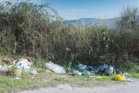contryside: Envelopes, tires, plastic bottles, and other waste left on the edge of a country road. Stock Photo