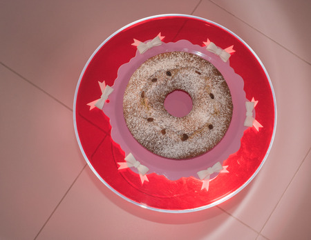 smal: sweet bunwith powdered sugar on red round table