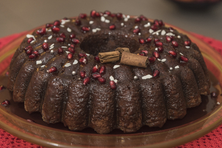 Donut in red wine, with cream of Aglianico, with pomegranate berries on handmade red lace. Italian red wine. Christmas cake.
