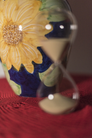Red tulips in blue vase, with yellow daisy, Vietri Sul Mare ceramic on red crochet doily and hourglass with sand.