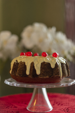Close up of Bundt Cake with white chocolate and candied cherries on glass splashback and red crochet table centerpiece.