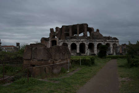 Roman amphitheater. External view of the arena and the ancient ruins. In the background the gray and cloudy sky of a rainy day.