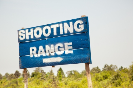 A blue sign directs tourists to the shooting range in Cambodia