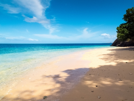 White sand beach with crystal clear blue water in the tropics