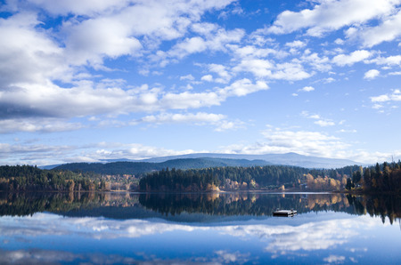 Reflections of the cloudy blue sky and forests mirrored in a calm mountain lake in a scenic landscape