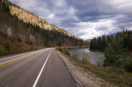 Tarred highway running through scenic forested mountains alongside a river under a cloudy grey sky