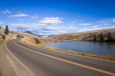 Tranquil Lake Between Long Road and Hills Under Light Blue Sky on one Sunny Day. Stock Photo
