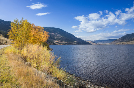 Tranquil lake surrounded by mountains under a cloudy sunny blue sky viewed from an embankment at the side of a road