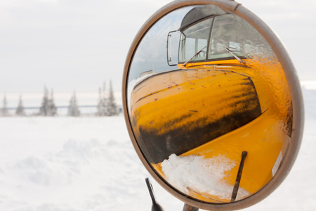 Yellow School Bus Reflected in Round Side View Mirror in Snowy Winter Landscape