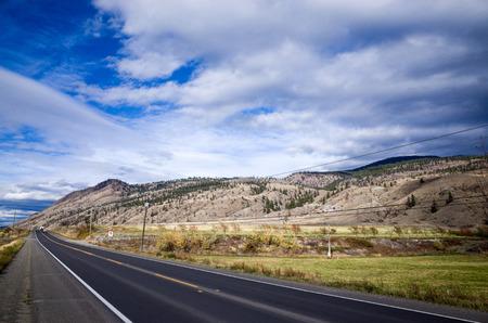 Empty asphalt highway receding into the distance through mountainous countryside under a cloudy blue sky