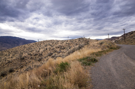 View from a gravel layby at the side of a tarred road of ominous grey storm clouds gathering over a mountain Stock Photo
