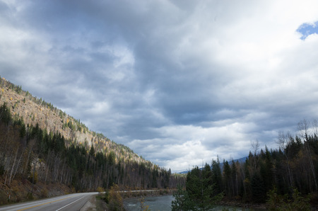 Mountain highway winding through forested peaks and valleys following a river under a cloudy grey sky