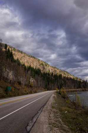 Deserted forested asphalt mountain road under a threatening overcast grey cloudy sky winding off into the distance