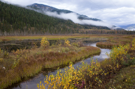 River meandering through a mountain valley with forested peaks shrouded in cloud in a scenic landscape view Stock Photo