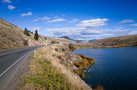 Tarred highway skirting a scenic tranquil blue mountain lake under a cloudy blue sky in mountainous terrain