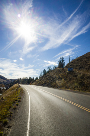 Sunburst above an empty tarred road in forested mountainous terrain Stock Photo
