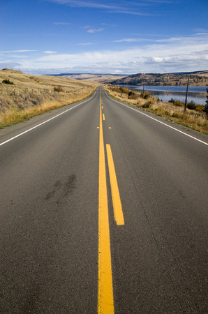 Straight country highway with yellow markings receding into the distance alongside a lake towards low hills under a blue sky