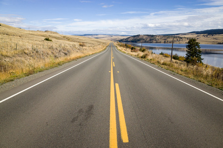 Yellow markings on a tarred highway leading straight off into the distance alongside a lake in low hills in a scenic landscape