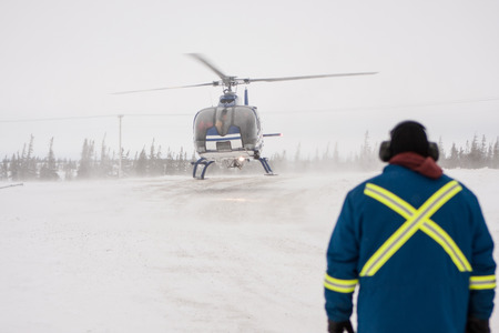 Helicopter Landing at Airport in Snowy Location with Ground Marshall in Foreground Wearing Safety Jacket