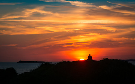 Sunset on the coast with a meditating man. Man silhouetted against a colourful sky with clouds Stock Photo