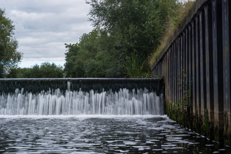 Weir across River Avon near Melksham. Water falling over artifical waterfall forming flood defense before town in Wiltshire, England, UK