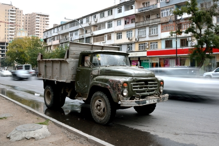 baku: BAKU, AZERBAIJAN - NOVEMBER 14 2013 Old truck crawling up hill in Baku, capital of Azerbaijan. An old soviet truck with modern traffic showing movement blur Editorial