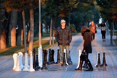 passtime: SUMGAIT, AZERBAIJAN - JANUARY 17 2014 Couple playing street chess in Sumgait, Azerbaijan. A couple play a game of street chess in a park in central Sumgait, around 30km from the capital, Baku Editorial