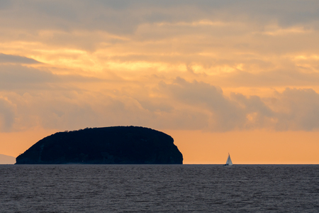 steep holm: Sunset behind Steep Holm Island in the Bristol Channel, with yacht. Spectacular sky and clouds seen from Weston-super-Mare in Somerset, UK, at high tide