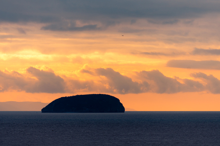 Sunset behind Steep Holm Island in the Bristol Channel. Spectacular sky and clouds seen from Weston-super-Mare in Somerset, UK, at high tide