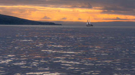 Sunset behind Brean Down in the Bristol Channel, with yacht. Spectacular sky and clouds seen from Weston-super-Mare in Somerset, UK, with fort on peninsula