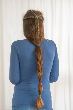 English plait renaissance hairstyle for long hair. Traditional plait style modelled by girl with very long golden hair Stock Photo